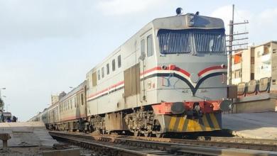 Photo of شابين في إحدى محطات القطار في مصر فوق قطار متحرك حيث يقومان بحركات بهلوانية بشكل خطير